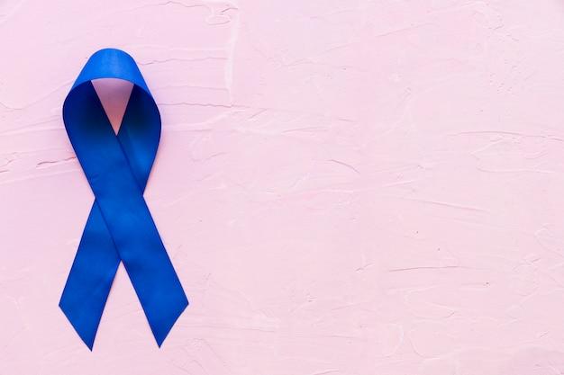 Ciemny niebieski wstążka świadomość na różowym szorstkim tle