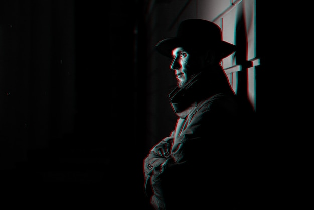 Ciemny portret mężczyzny w płaszczu z kapeluszem w nocy na ulicy. czarno-biały z efektem wirtualnej rzeczywistości 3d glitch
