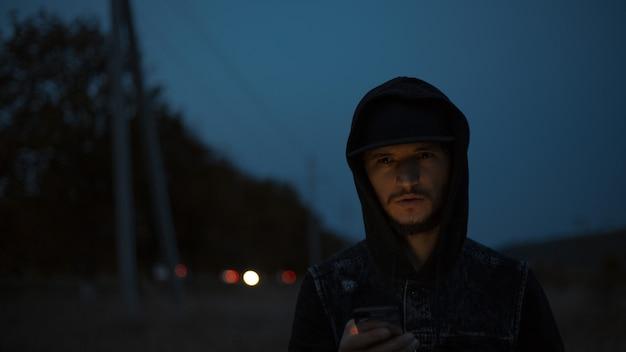 Ciemny portret młodego poważnego faceta, który stoi na ulicy w nocy ze smartfonem w ręce