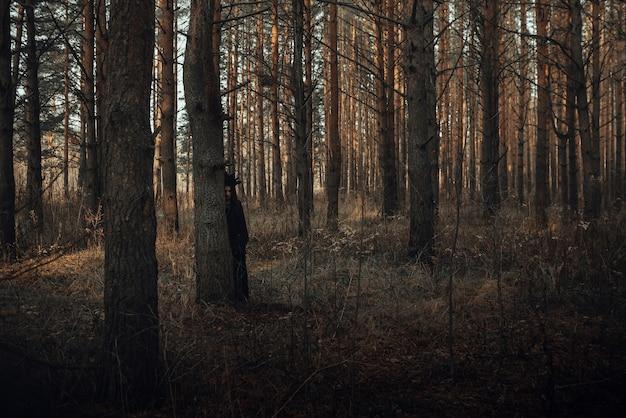 Ciemny portret strasznej wiedźmy w czarnym garniturze w lesie pod drzewem