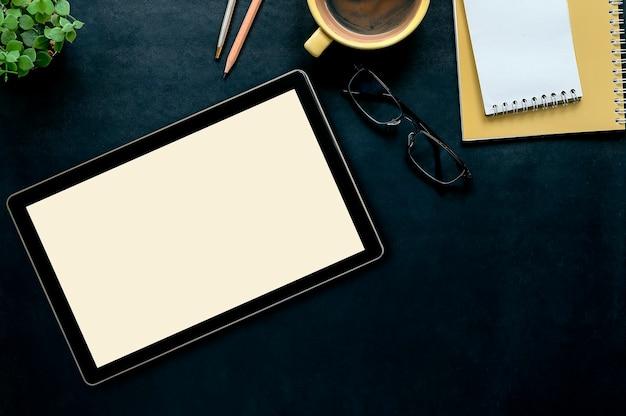 Ciemny rzemienny biurowy biurko z pastylką, filiżanką kawy, ołówkiem, szkłami i żółtym notatnikiem