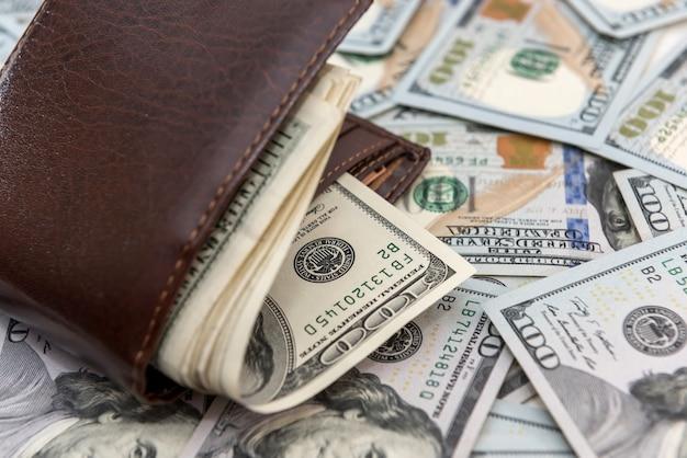 Ciemny skórzany męski portfel pełne banknoty dolarowe jako tło finansowe, koncepcja oszczędności