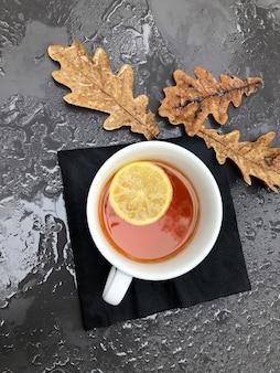 Ciemny stół z kroplami wody po deszczu i jesienne liście z kubkiem herbaty z cytrynami.