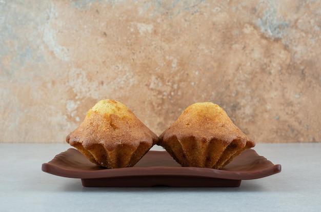 Ciemny talerz dwóch pysznych babeczek na białym stole.