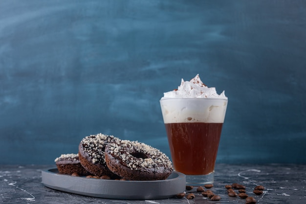 Ciemny talerz pączków czekoladowych z posypką kokosową i pyszną kawą na marmurowym tle.