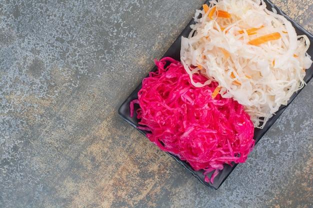 Ciemny talerz pełen czerwonej słonej kapusty na marmurowym tle. zdjęcie wysokiej jakości
