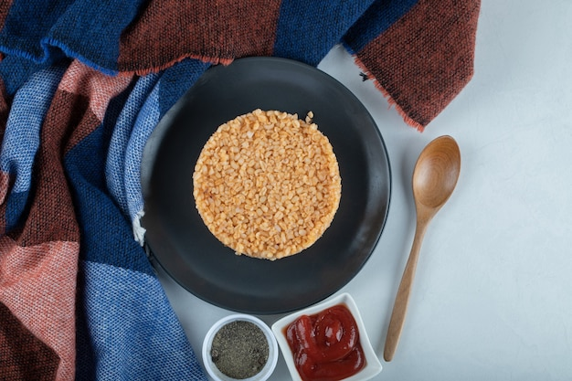 Ciemny talerz pełen kaszy bulgur z pieprzem i keczupem