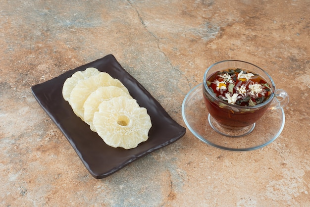 Ciemny talerz pełen suszonego zdrowego ananasa i filiżanki herbaty