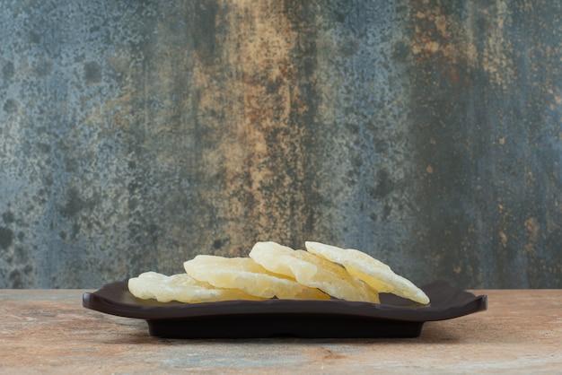 Ciemny talerz pełen suszonego, zdrowego ananasa