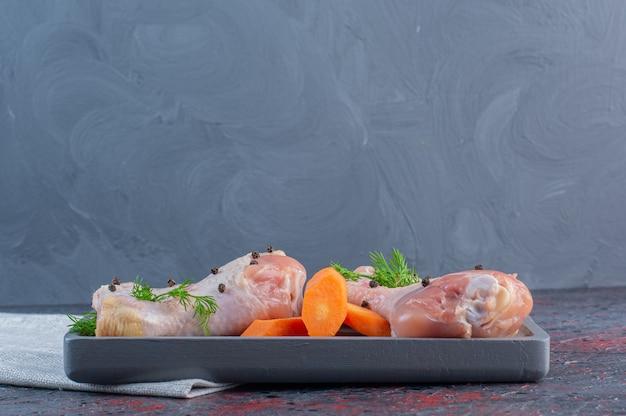 Ciemny talerz podudzi z surowego kurczaka na marmurowej powierzchni