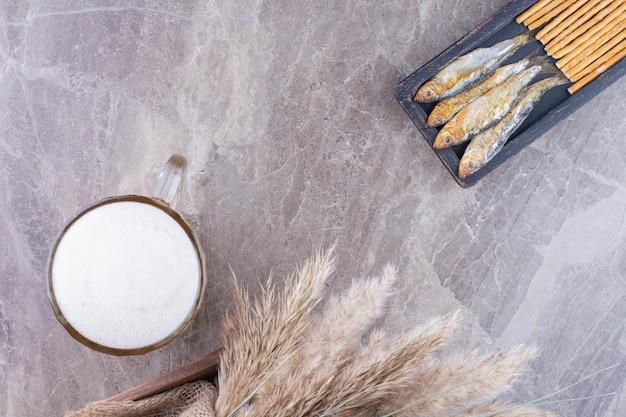 Ciemny talerz przekąsek i spienione piwo na marmurowej powierzchni. zdjęcie wysokiej jakości