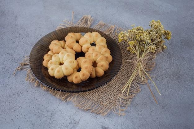 Ciemny talerz słodkich ciasteczek w kształcie kwiatu na kamiennej powierzchni.
