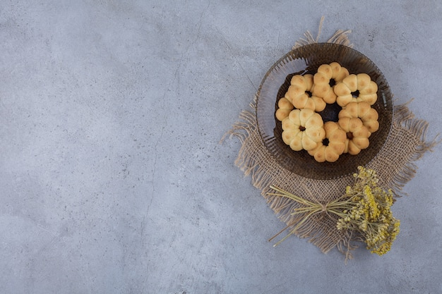 Ciemny talerz słodkich ciasteczek w kształcie kwiatu na kamiennym tle.