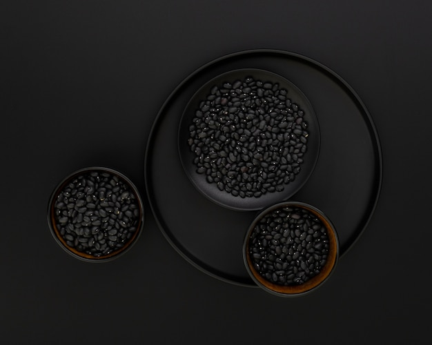 Ciemny talerz z czarnymi miskami fasoli na czarnym tle