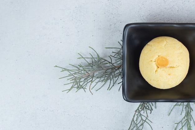 Ciemny talerz z okrągłym słodkim ciastkiem na białej powierzchni