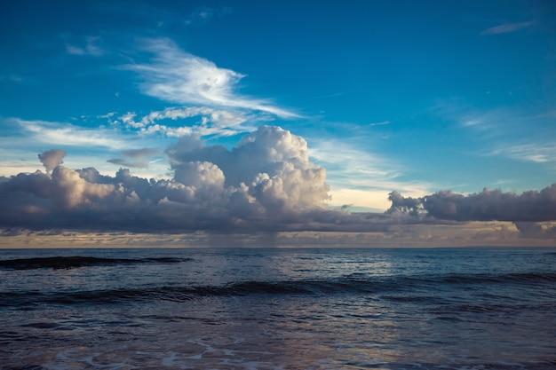 Ciemny zachód słońca nad morzem z pięknymi chmurami
