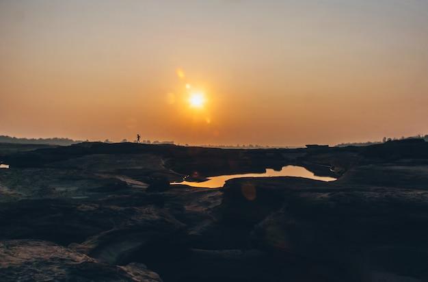 Cień biegacza biegnie przez słońce i suchy ląd