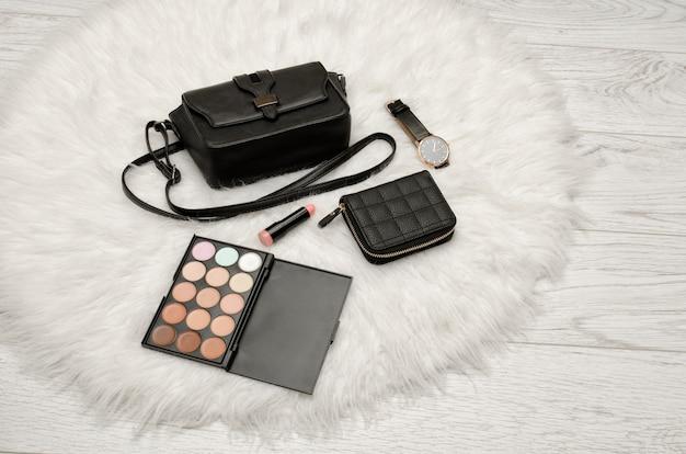 Cień do powiek, portfel, szminka, zegarek i czarna torebka na białym futrze. koncepcja mody