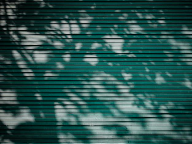 Cień drzewa na ścianie z blachy.