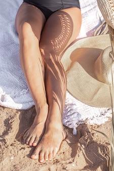 Cień gałęzi palmowych na ciele kobiety relaksującej się na plaży. koncepcja odpoczynku i lata.