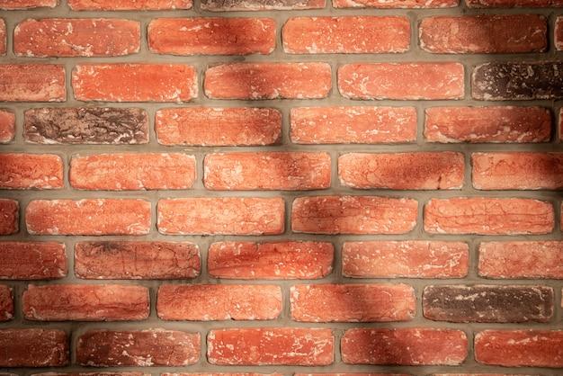 Cień i światło z okna na ścianie z czerwonej cegły