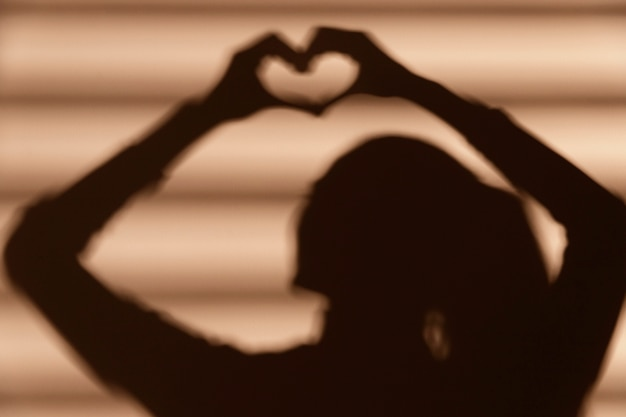 Cień kobiety robiącej serce