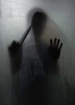 Cień mordercy horroru trzymającego ostry nóż za matowym szkłem w łazience