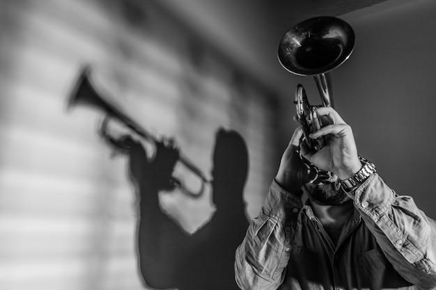 Cień muzyka jazzowego grającego na trąbce. koncepcja muzyki jazzowej.