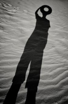 Cień na piasku człowieka z kołem zamiast głowy