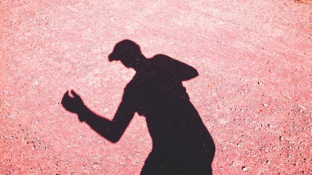 Cień na ziemi biegacza z czapką w lecie z dużą ilością ciepła.