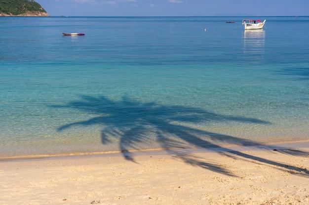 Cień palmy kokosowe nad piaszczystą plażą w pobliżu niebieskiej wody morskiej na wyspie koh phangan, tajlandia. koncepcja lato, podróże, wakacje i wakacje