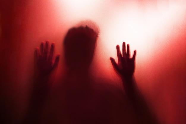 Cień ręki ducha za matowym szkłem