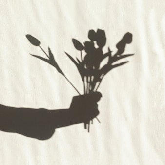 Cień ręki trzymającej tulipany