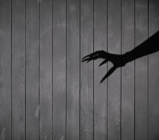 Cień ręki wiedźmy na czarnym tle