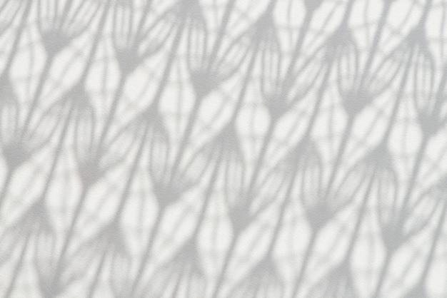 Cień wzorzystego tiulu pada na białą drewnianą powierzchnię