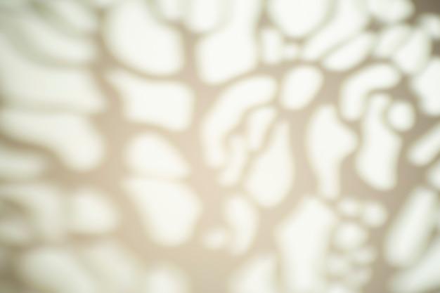 Cień z liści drzewa na białej ścianie przy słonecznej pogodzie z jasnym światłem. efekt nakładki cienia na zdjęcie.