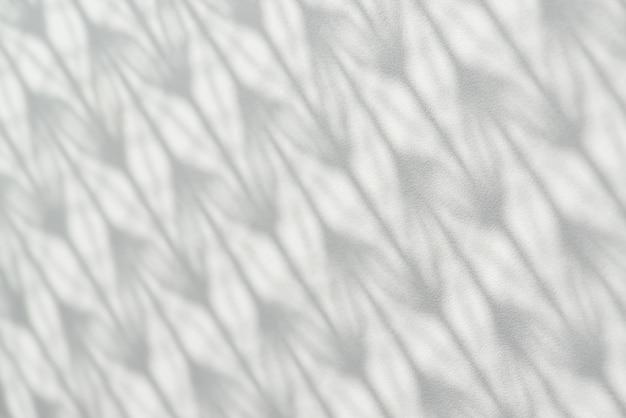 Cień z wzorzystego tiulu spada na białej powierzchni drewnianej.