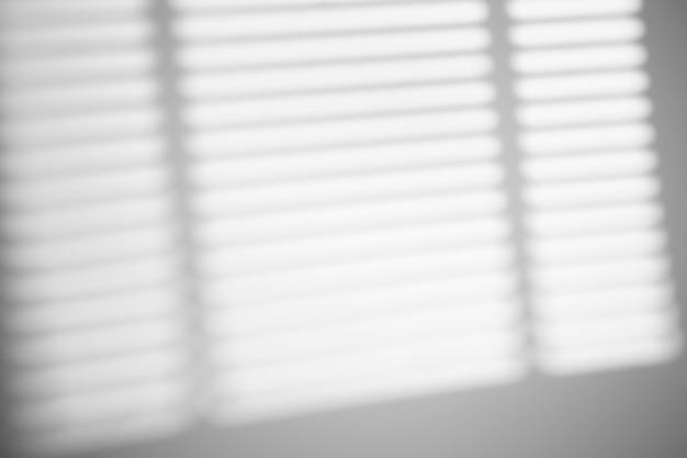 Cień z żaluzji okiennych na białej ścianie przy słonecznej pogodzie z jasnym światłem. efekt nakładki cienia na zdjęcie.