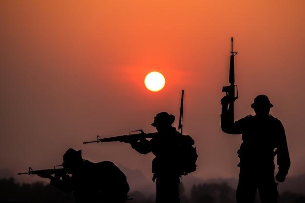 Cień żołnierzy na polu bitwy patrolujących o zachodzie słońca