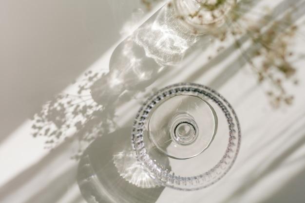Cienie na białym tle ze szkła i kwiatów. suszone kwiaty w szklanym wazonie w promieniach światła. dom.