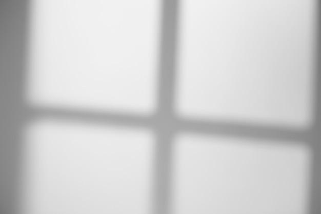 Cienie ram okiennych i krat na ścianie