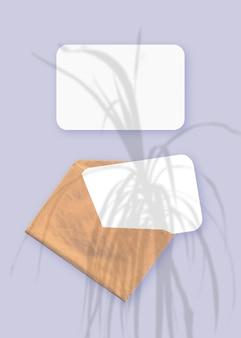 Cienie roślin na kopercie z dwoma arkuszami teksturowanego białego papieru na fioletowym tle stołu