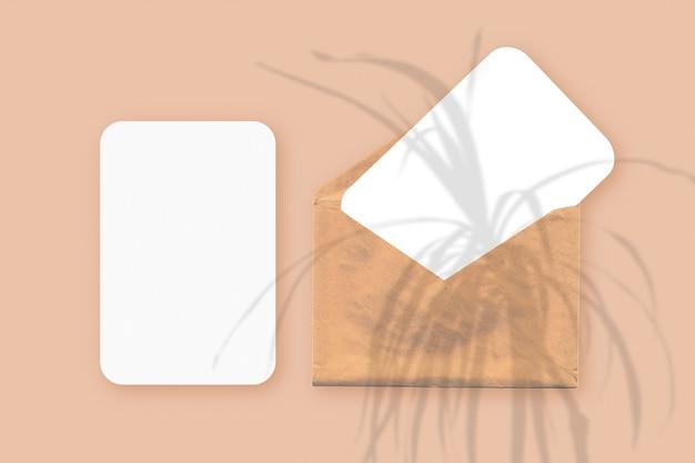 Cienie roślin na kopercie z dwoma arkuszami teksturowanego białego papieru na pomarańczowym tle stołu