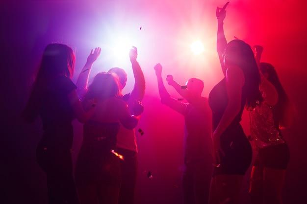 Cienie. tłum ludzi w sylwetce podnosi ręce na parkiecie na neonowym tle. życie nocne, klub, muzyka, taniec, ruch, młodzież. fioletowo-różowe kolory i poruszające dziewczyny i chłopcy.