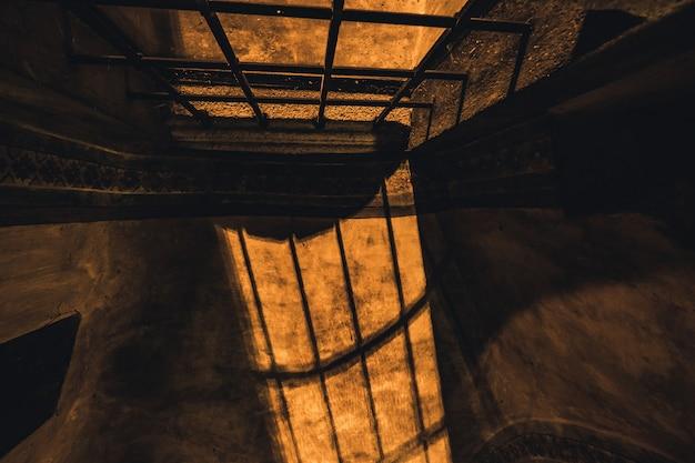 Cienie z kraty w tajemniczym korytarzu w starym pokoju