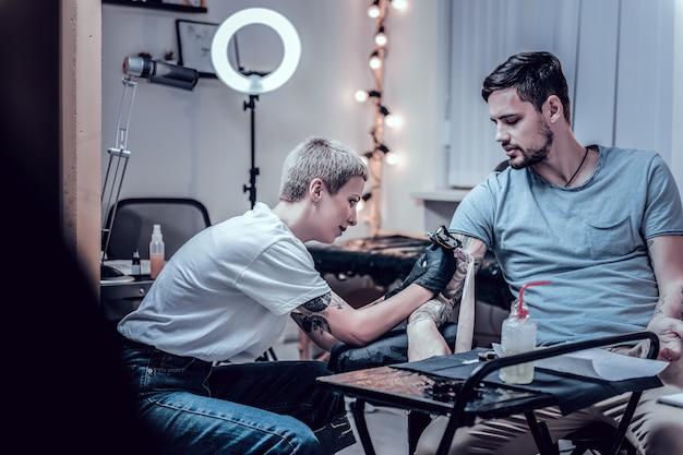 Cieniowanie do tatuażu. uśmiechający się, uważny profesjonalny mistrz tatuażu pracujący z niedokończoną pracą tatuażu na dłoni swojego stałego klienta