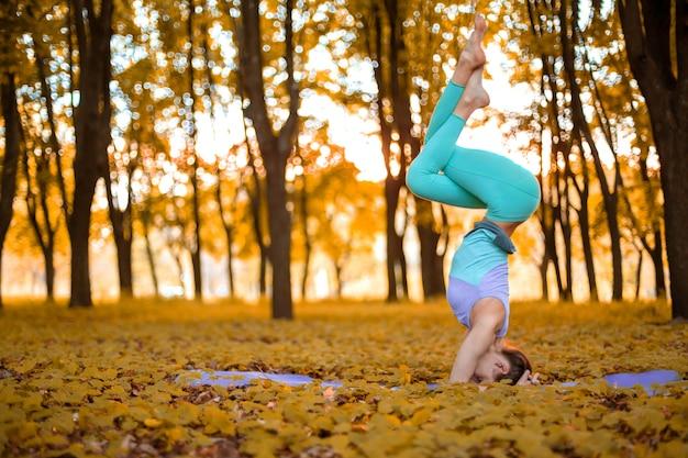 Cienka brunetka dziewczyna stoi w ćwiczeniu headstand, garuda salamba sirsasana stanowią w parku jesienią