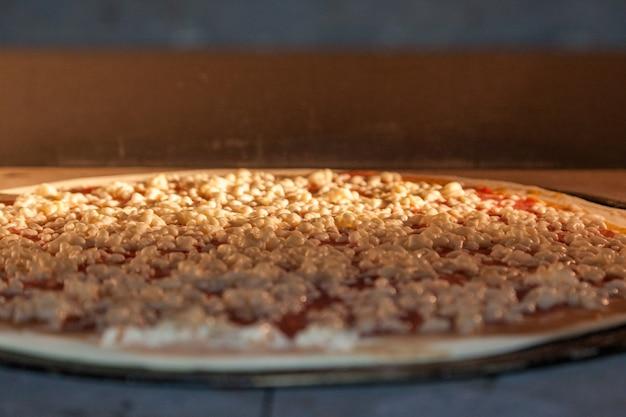 Cienka pyszna pizza wypiekana jest w piekarniku. gotowanie pizzy w pizzerii.