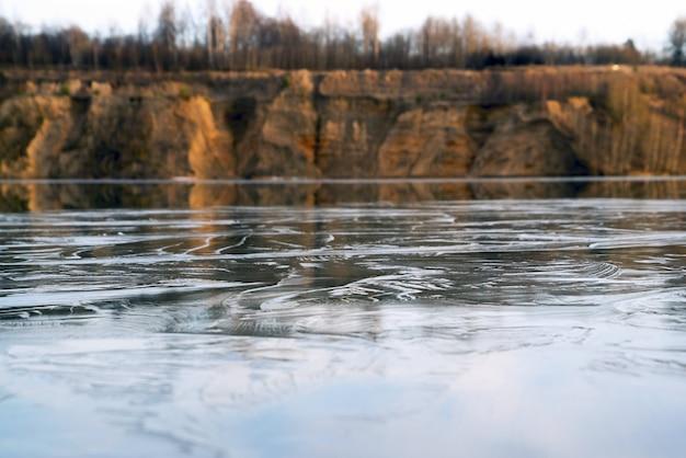 Cienki lód na wodzie z kamieniołomu. obwód leningradzki.