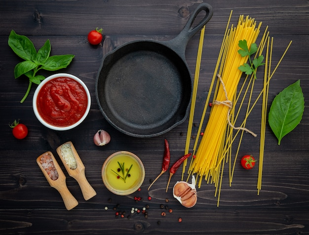 Cienki spaghetti na czarnym drewnianym tle.